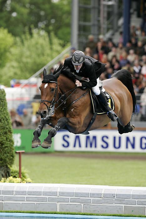 Marcus Ehning & Kuechen Girl showing an incredible reach jumping the water jump