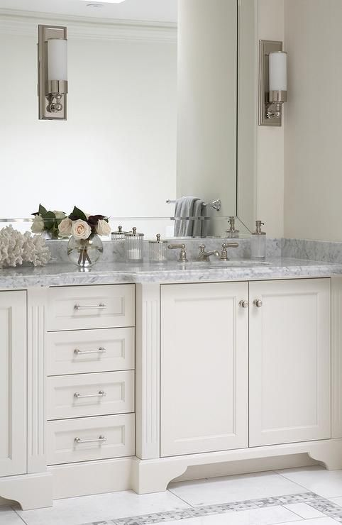 Sophisticated bathroom features a white vanity topped with ...