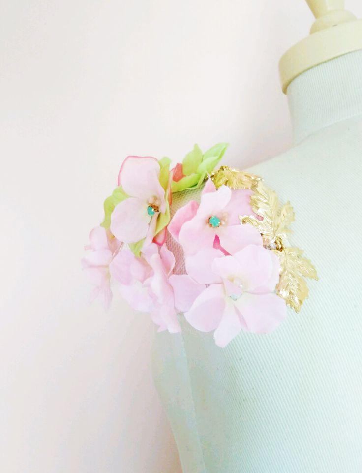 Invitada con hombreras de flores y hojas de metal dorado.