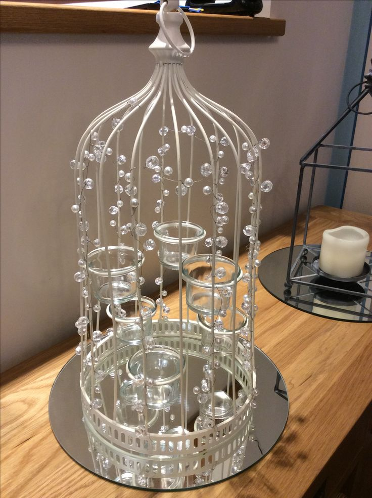 Tall pearl birdcages with mirror plates and t-light holders on centre £7 hire fee 10 available