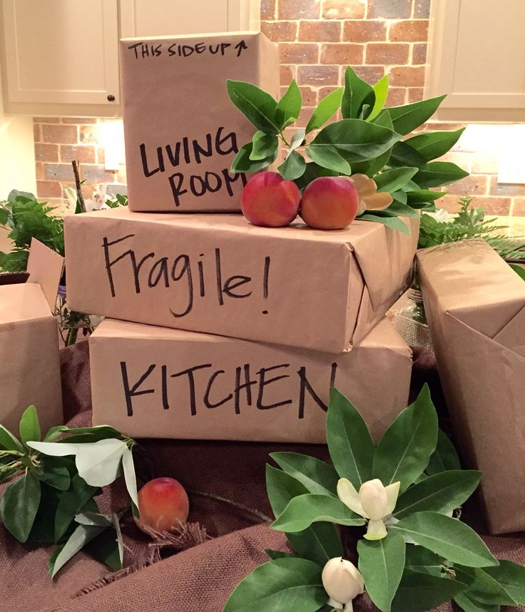 Moving boxes centerpiece for a going away party. Moving from Mississippi to Georgia so I added magnolia leaves and peaches to represent both states.