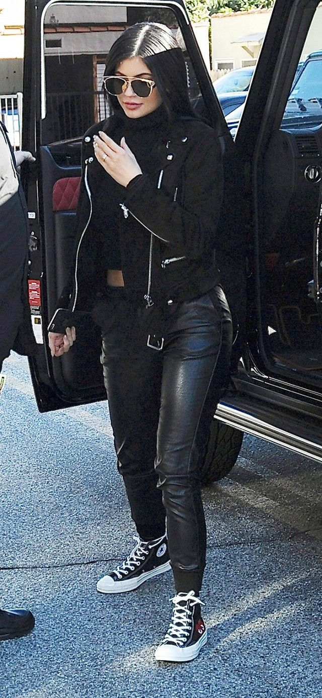 Kylie Jenner wears a cropped turtleneck, moto jacket, leather pants, and high-top sneakers