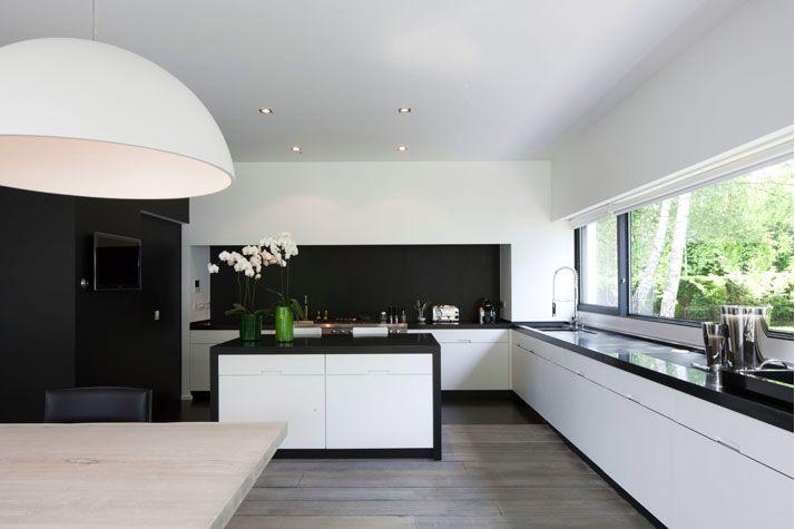 kitchen long window black countertop white cabinets