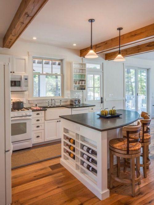 Holzbalkendecken und Anhänger Beleuchtung Punkte auf die weiß getünchte Küche und Kücheninsel auf Holzböden ausgesetzt.
