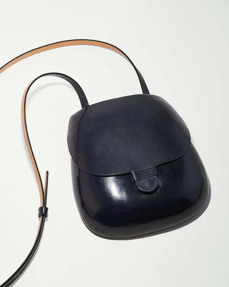 Of A Different Mold / Keeping in line with rigorous forms and unconventional detail, Lemaire's play on the classic camera bag is no different. As if cast from a surrealist objet d'art, hand-shaped cow hides over wooden molds create pared-down contour...