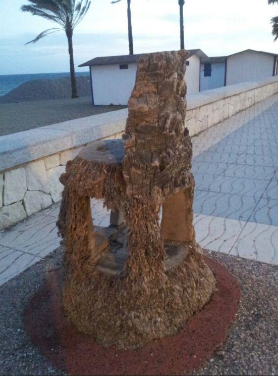 Original silla hecha del tronco de una palmera. Pensar en los ciudadanos, relax frente al mar.