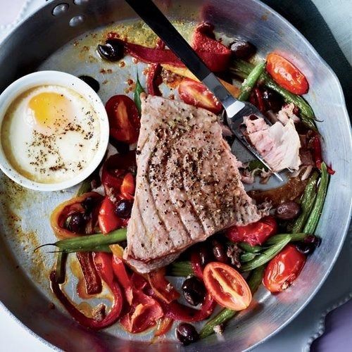 Gwyneth Paltrow transforms one of her favorite salads, the Niçoise, into a hearty one-dish dinner by roasting tuna steaks on a tangle of beans, tomatoes, anchovies and olives.