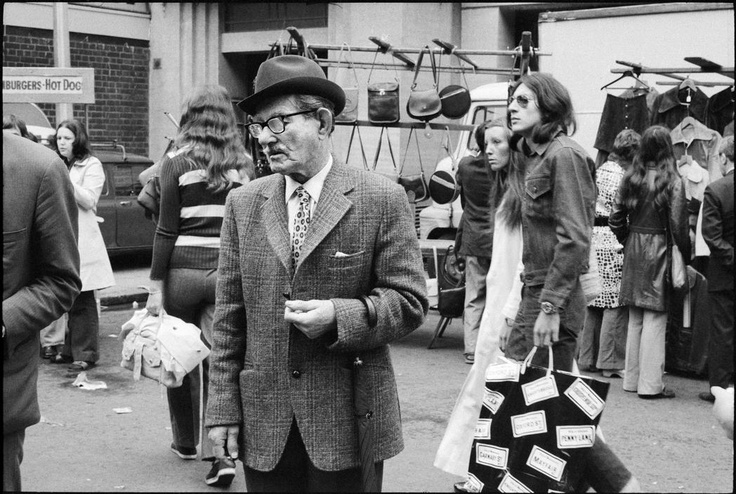 an Berry G.B. ENGLAND. London. Whitechapel. A very dapper gentleman, complete with trilby hat and furled umbrella, stands and looks at a stall in the street market, surrounded by other shoppers. 1972