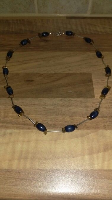 Necklace with silver tubes, tigers eye chips and bkue wooden beads.