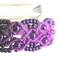 """Náramek je vytvořený technikou micromacramé ze dvou fialových přízí - bavlna a satén. Ozdobou jsou drobné fialové kovové korálky s perletovou úpravou. Šířka náramku je 2 cm, délka 19 cm vč. zapínání na šitý """"knoflíček""""."""