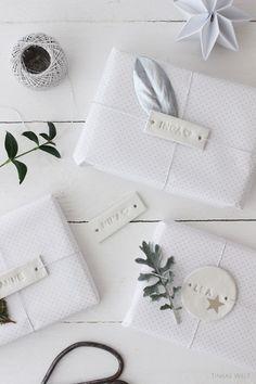 Nicht nur zu Weihnachten eine tolle Idee… Namensanhänger für die Geschenke - Ihr benötigt Modelliermasse in weiß (z.B. von Creall für den Innenbereich, lufttrocknend, kein Brennofen nötig, umweltfreundlich. Inhalt: 1 kg kostet ca. 4,00 Euro), schmales Geschenkband, Buchstabenstempel (z.B. für Plätzchen bekommt man für 9,00 Euro bei amazon), dezentes Geschenkpapier in weiß