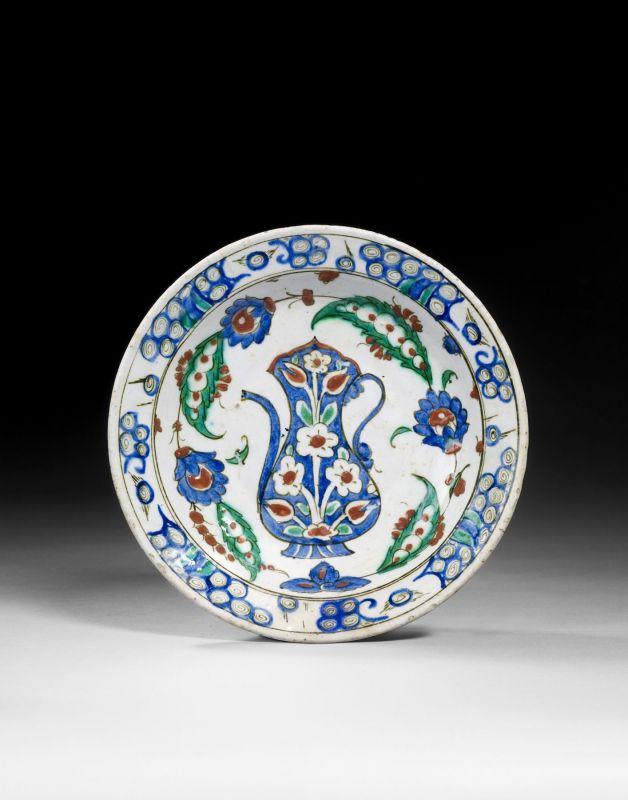 """PLAT À L'AIGUIÈRE, IZNIK, VERS 1580-1590  Plat """" tabak """" décoré en polychromie et engobe rouge ("""" bol """") sur fond blanc d'une aiguière aux motifs floraux bleus, entourée d'une couronne de palmes et de fleurs. Sur le marli, vagues et rochers bleus et turquoise. Au revers, huit motifs et fruits bleus et verts.  Diamètre : 30 cm. (11 ¾ in.)    AN IZNIK POTTERY DISH WITH AN EWER, CA.1580-1590"""