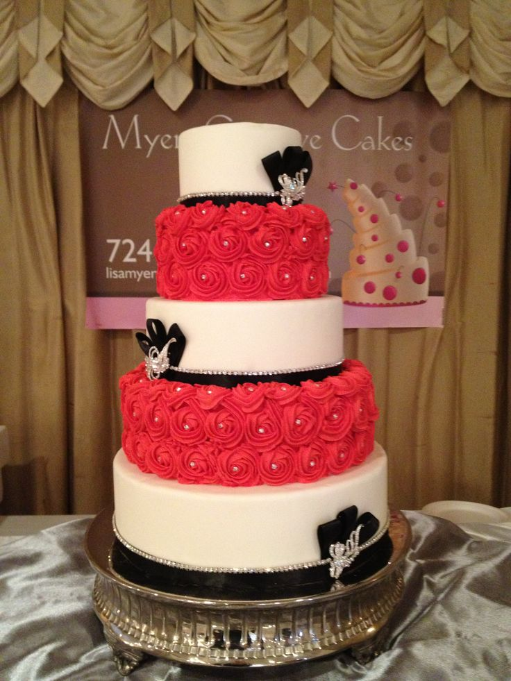 Rosette cake - 5 tier white fondant and red buttercream rosettes with rhinestone accents and trim.