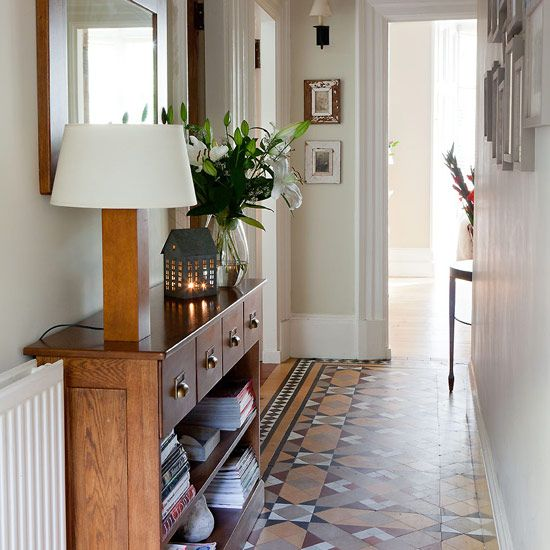 Victorian tiled flooring in hall with console table, table lamp and wall mirror.