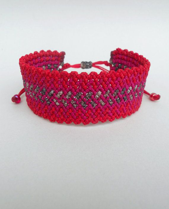 This handmade macrame bracelet is made out of red,fuchsia and metallic brown waxed string. At the end it is adorned with seed beads. It is