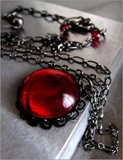 Deep blood red domed glass pendant necklace with black bezel setting on long black gunmetal chain, very Goth Gothic style for vampire lovers.