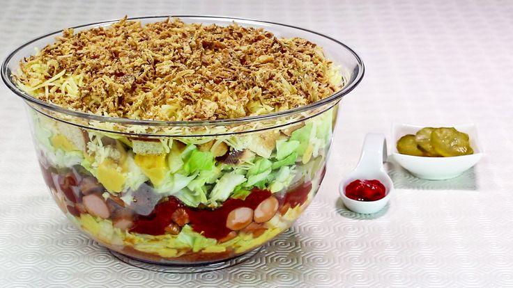 <p>Der Hot Dog in XXL-Variante wird hier als Salat nachempfunden. Die Zubereitung ist einfach, das Ergebnis extrem lecker und auf jeder Party willkommen! Unbedingt mal ausprobieren!</p><p><b><br></b></p><p><b>Zutaten:</b><br></p><p>2 große Zwiebeln<br>500 g Hot Dog Würste, Wiener oder Bockwürste<br>1 kleiner Eisbergsalat<br>5 Hot Dog Brötchen, alternativ Hamburger Brötchen&...