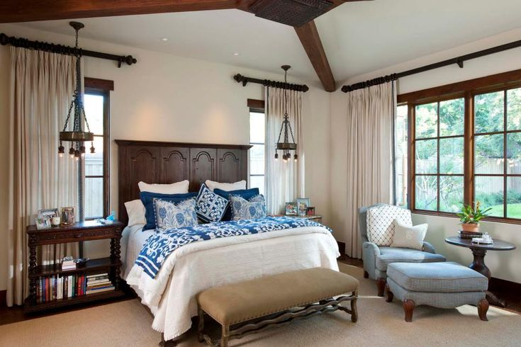A traditional wood headboard with Spanish design centers this sophisticated yet rustic bedroom. Architectural details, like exposed wood beams and wood window trim, add warmth to the space. Simple white bedding pairs with cobalt blue pillows and quilt for Mexican-inspired color.