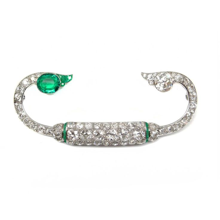 Art Deco emerald and diamond fibula design brooch by Cartier, Paris c.1925,  the pave-set old-cut diamond curving panel with six principal diamonds and calibre emerald line detail, the diamond curves terminating in either an oval cut emerald or brilliant cut diamond with foliate flourish, mounted in platinum, serial no.C8082, original Cartier case  Length 9cm  Weight: 24.5g