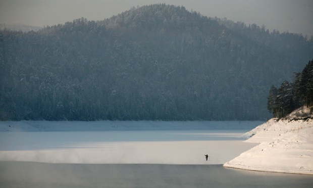 A man fishes on newly formed thin ice that covers a part of the Yenisei river as the temperature dropped to -26C outside Krasnoyarsk in Russia