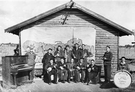 Members of the Hay internment camp orchestra (band) featuring an upright piano, drum kit, four banjos, trombone, baritone saxophone, clarinet, cornet and trumpet.