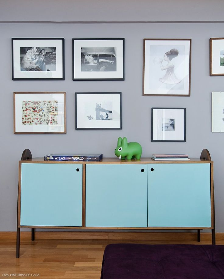 Buffet retrô azul clarinho e parede  cinza com fotos e ilustrações do acervo da família.