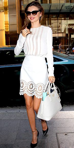 Miranda Kerr steps out in a white blouse with sheer panels, tucked into a perforated white skirt, plus a matching Prada and black ankle-strap heels.