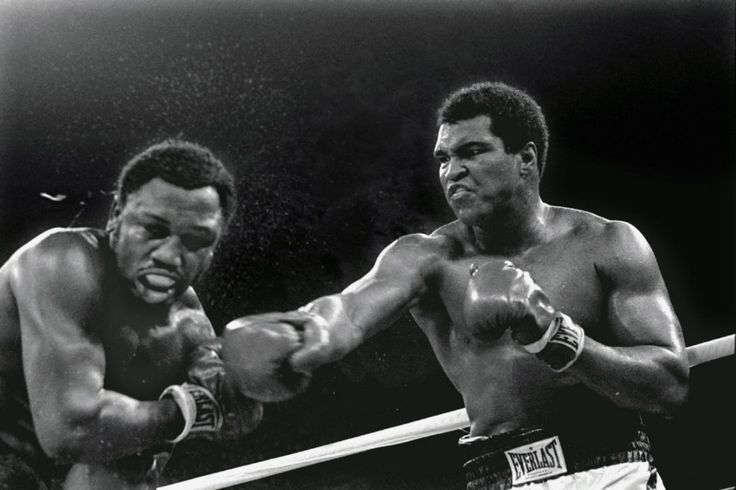 "Oct. 1, 1975: Sweat spray flies from the head of challenger Joe Frazier as heavyweight champion Muhammad Ali connects with a right in the ninth round of their heavyweight title fight in Manila, Philippines. Ali won the fight, infamously dubbed the ""Thrilla in Manila,"" on a decision to retain the title."