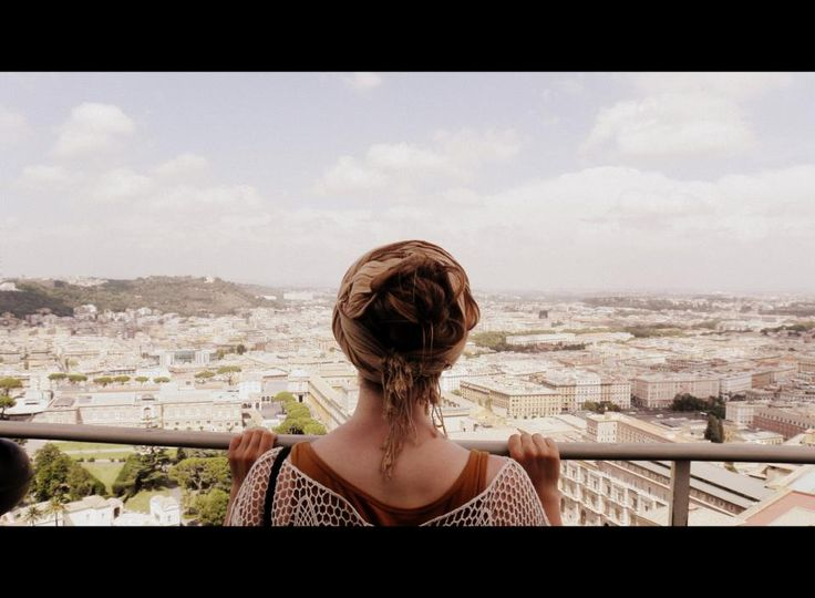 fotografía sin rostro. Es una foto sacada de una turista en la cúpula de la Basílica de San Pedro. Hay miles de personas que quieren subir para ver las vistas desde la cúpula de San Pedro. Sin identificar la persona la foto pregunta: Qué es el encanto en ver ciudades desde un punto alto?