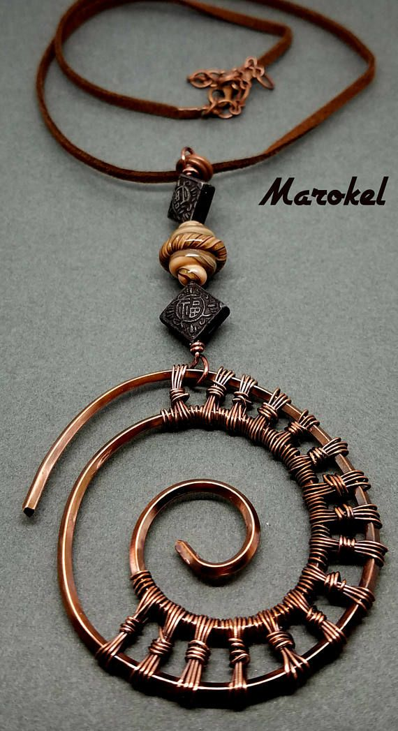 I really like the colors on this. This pendant is made with a heavy gauge square copper wire that has been coiled, oxidized and textured. Copper wire is wrapped around the coil to resemble an ammonite shell. When I oxidized it, I tried to go for an ombre style, darker on the outer edges. Coil