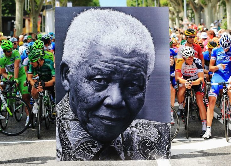 The peloton wait behind a large picture commemorating the birthday of former South African President Nelson Mandela before stage eighteen of the 2013 Tour de France