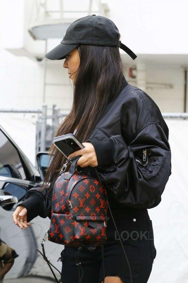 Kourtney Kardashian wearing Alexander Wang Cropepd Bomber Jacket, Louis Vuitton Palm Springs Mini Backpack, Good American Raw Edge Jeans, Fan Merchandise Yeezus Dat Hat