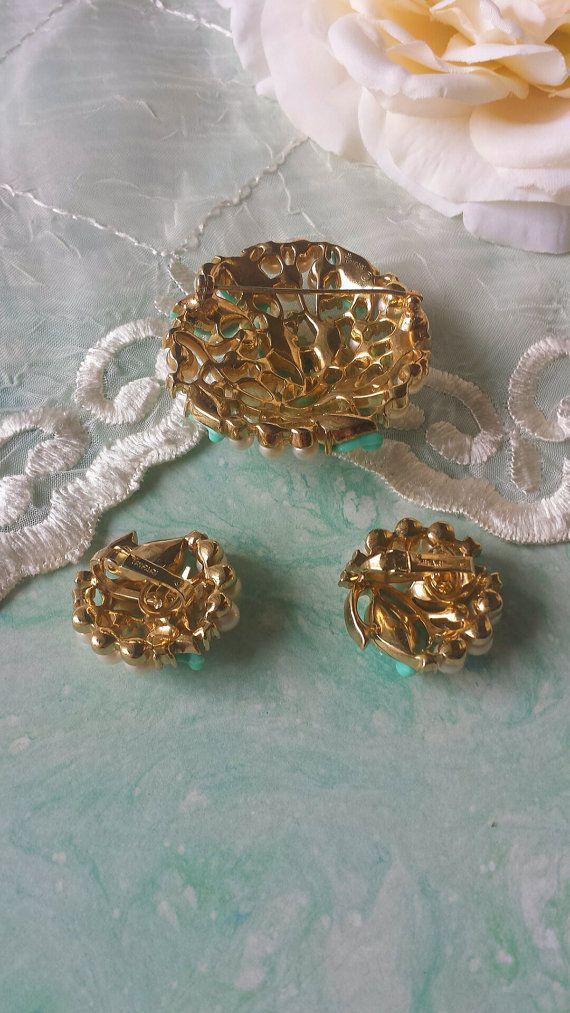 Corona vintage Trifari Parure Perle Lucite strass collezione Classic del 1960...   Si tratta di una bella serie di Crown Trifari con foglie Lucite di perle finte, turchese, chiaro strass in tono oro. Collana, bracciale, spilla e orecchini tutti ottime condizioni vintage. La collana è curvo quindi si adatta bene. Può essere indossato come il tag è ancora acceso, non posso essere sicuro.  Collana 16 x 5/8 J-ciclo Bracciale 7 x 3/4 déployante Spilla 2 attraverso a cupola Orecchini 1 at...