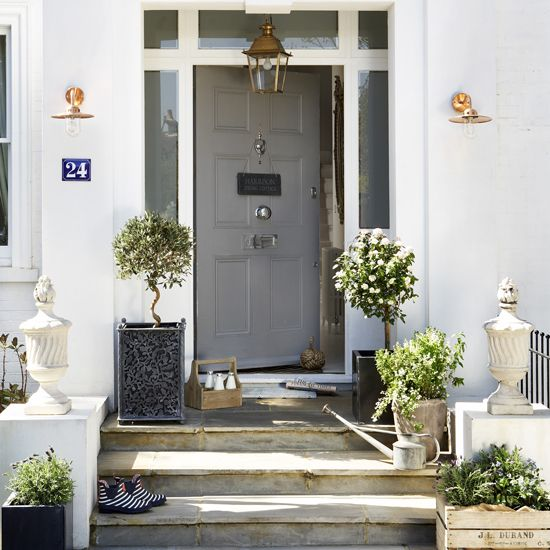 A pair of stone urns will add an elegant symmetry to a traditional front door. Copper light fixtures and container planting have added another welcoming dimension to this classic grey entrance