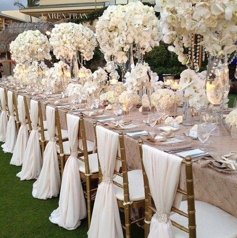This is a dreamy, TO DIE FOR, tablescape with whites, champagnes and golds. The lush tall centerpieces with draping orchids and crystals and the flowing chair ties make this a must have look.