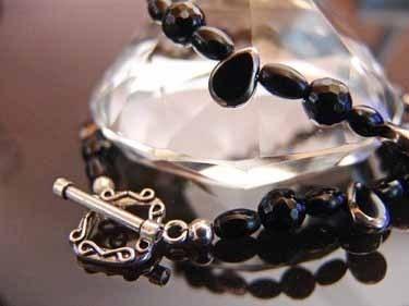 Facettierte Perlen aus Onyx, unterbrochen von kleinen Oliven (Onyx) und Tropfen aus Glas... die Glastropfen haben einen Silberrand und sind galvani...