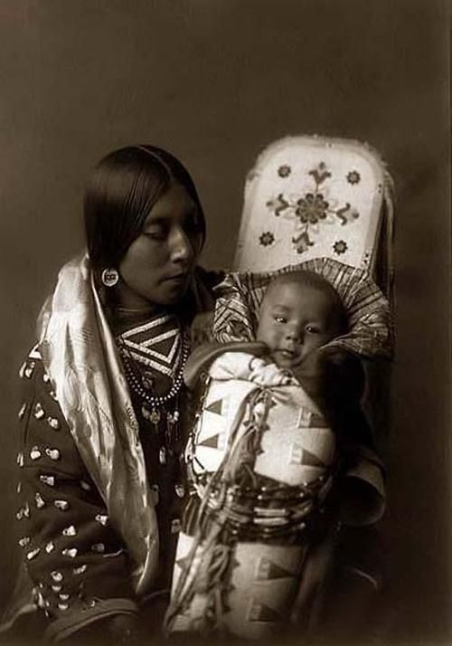 Indian Mother holding her Child. It was taken in 1908 by Edward S. Curtis. The image shows a Portrait of a Native American woman in a half-length, seated, facing right, position holding her baby in a beaded cradleboard.
