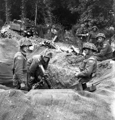 A 3-inch mortar crew of The Canadian Regina Rifle Regiment in Normandy, 9 june 1944. Their Carrier can be seen in the background.