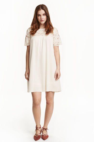 Jurk met kant: Een korte jurk van geweven crinkleviscose met kanten schouderpassen en mouwen. De jurk heeft een splitje met een knoop in de nek. Gevoerd met tricot.