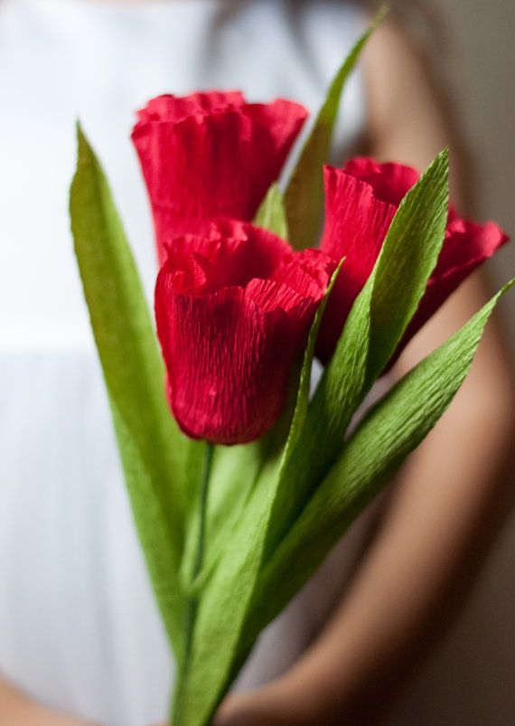Tulips remind me of spring! This lovely tulip is made out of crepe paper and will never wilt. Brighten someones day with a bouquet of these happy flowers. This tulip comes on a floral wire stem and is about 9 inches tall. It has two crepe paper leaves. It looks lovely on its own or in a bundle tied with a bow. This listing is for a single flower. Add more to your cart for a bouquet. Available in red, pink, yellow, orange or purple. If you have another color in mind, ask me! I may be able to…