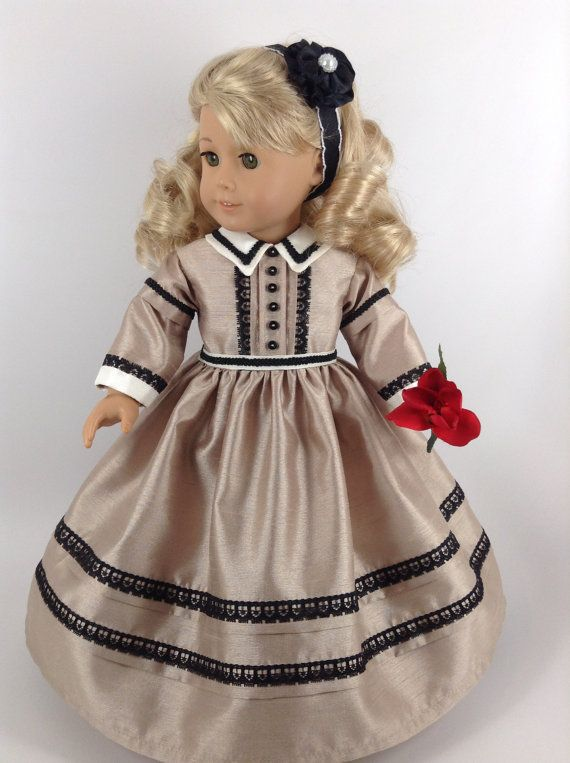 Handmade dress, pantaloons, and ribbon flower hair band for American Girl and other similar 18-inch dolls.  This one-of-a-kind 1800s Civil War Era dress in colors of taupe, black, and cream is made of shantung (dress, collar, & cuffs). Features include a lined bodice, slightly dropped shoulders, bodice placket with tucks trimmed in black lace and accented with six black buttons, a cream-colored collar trimmed in braid, banded double sleeves trimmed with braid on the upper sleeve and lace on…