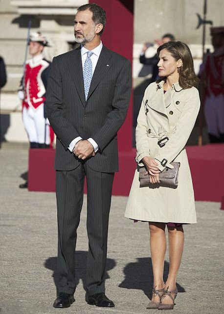 Spanish Queen Letizia wrapped up against the winter chill in her classic trench coat, which she paired with suede mushroom-colored heels with a matching metallic clutch. King Felipe of Spain, looked dapper in a pin-striped suit, white shirt and blue floral tie, as they received the President and First Lady of Israel at Royal Palace on November 6, 2017 in Madrid, Spain.