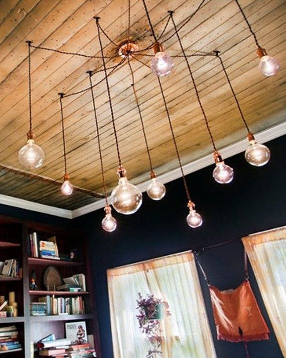 Swag black cords for five or seven Edison bulbs out to hooks on ceiling, hanging down over dining table.