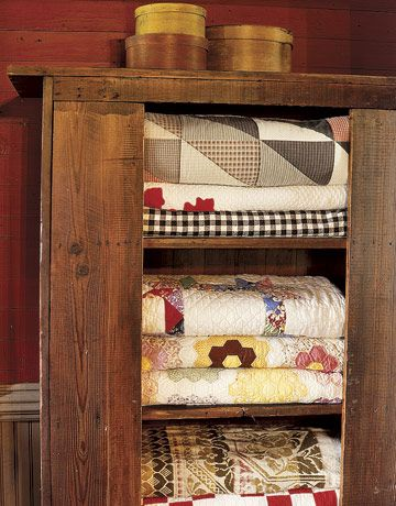 primitive cupboard full of quilts