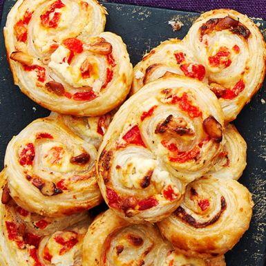 Av färdig smördeg går det att göra massa roliga och goda snittar. Som dessa frasiga munsbitar med italienska smaker, formade till snygga kringlor. Smördegen fyller du med färskost, parmesan, pinjekärnor och inlagd, grillad paprika. Lika goda kalla som ljumna!