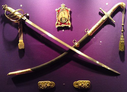 Sword in the left - offered by the Romanian Army to King Charles I, the Commander in Chief during the Romanian War of Independence, known worldwide as the Russo-Turkish War (1877-1878). Sword in the right - sword and girdle given to Charles I by Sultan Abdul Aziz on the occasion of his recognition as Prince of the United Romanian Principalities.