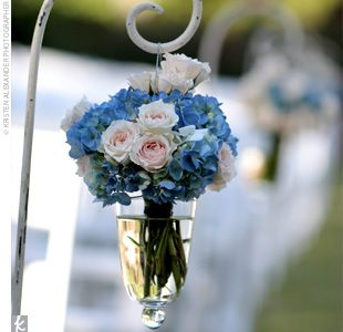 Shepherd's hooks with glass vases filled with blue hydrangeas and white roses lined the aisle.