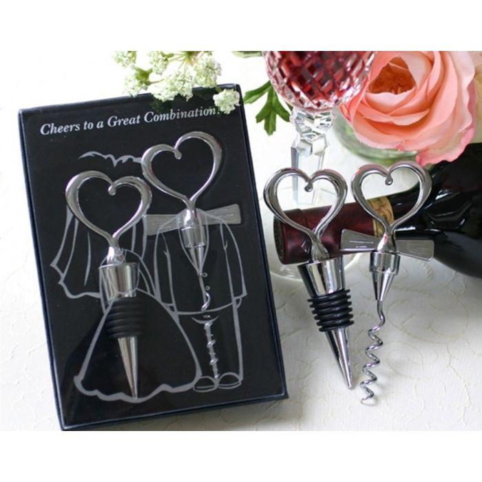 """Ce duo tire-bouchon et bouchon de vin en forme de cœur est présenté dans une élégante boite en acétate de couleur noire, avec le dessin d´un couple de mariés, le couvercle de la boite en plastique est transparent. Ce cadeau est trés original, le bouchon de vin représente la mariée et le tire-bouchon le marié. On remarque l´inscription """"Cheers to a gr..."""