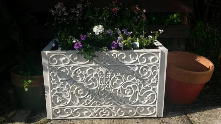 Glue rubber doormat onto 2-drawer filing cabinet, spray paint, and fill with soil for a planter!