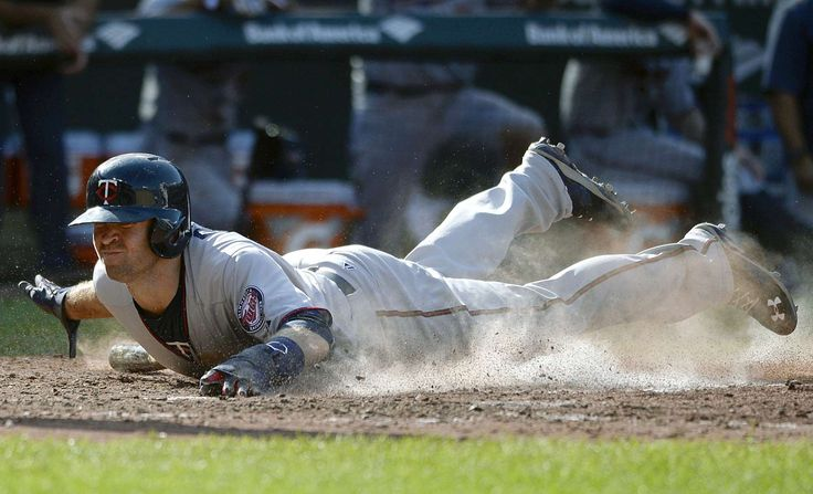 Dusty run -  Minnesota Twins second baseman Brian Dozier scores the tying run in the ninth inning against the Baltimore Orioles Aug. 23 in Baltimore. The Twins won 4-3 in 12 innings. -  © Tommy Gilligan/USA TODAY Sports